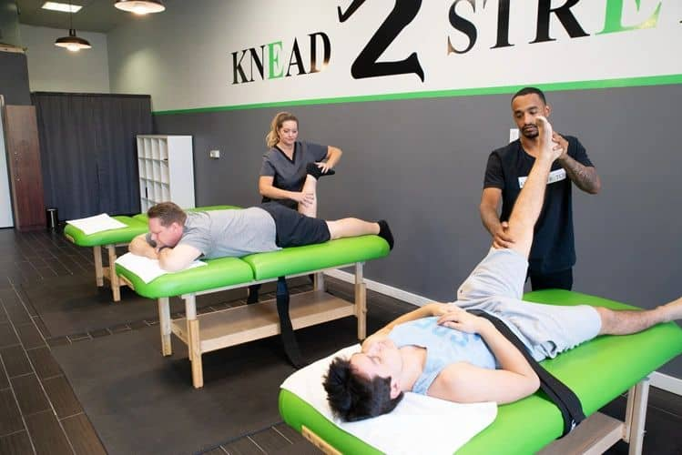 Two Knead2Stretch therapists helping stretch two male clients individually