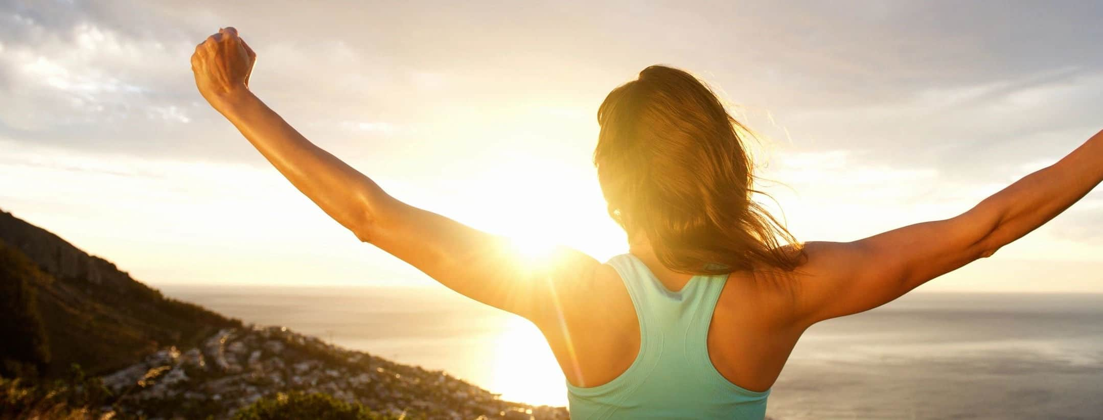 woman with outstretched arms watching the sunset over the ocean