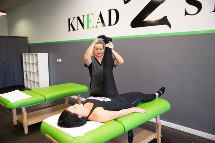 a Knead2Stretch therapist helps a female by stretching her left leg while the client lays on a table