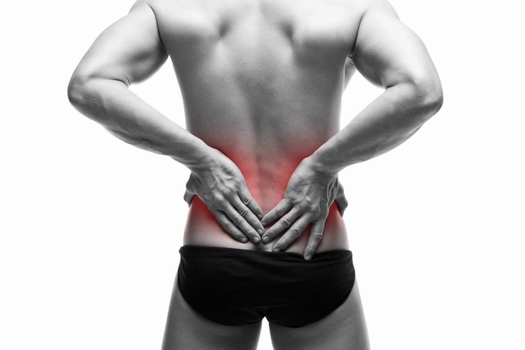 a man with his back to the camera puts his hands on a stylized red region of his lower back indicating he is in pain in that area