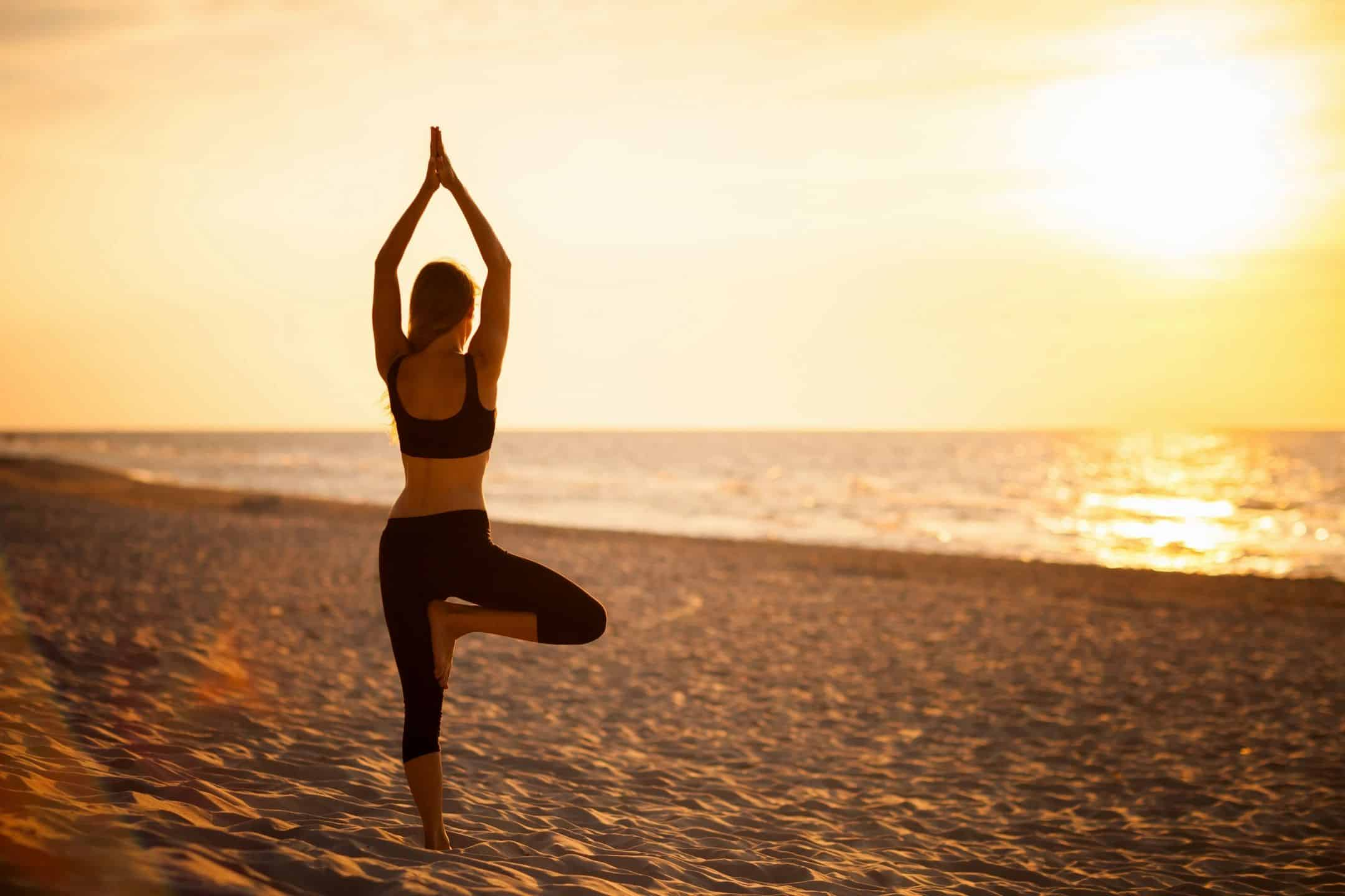 woman at beach stretching her arms above her head while standing on one leg