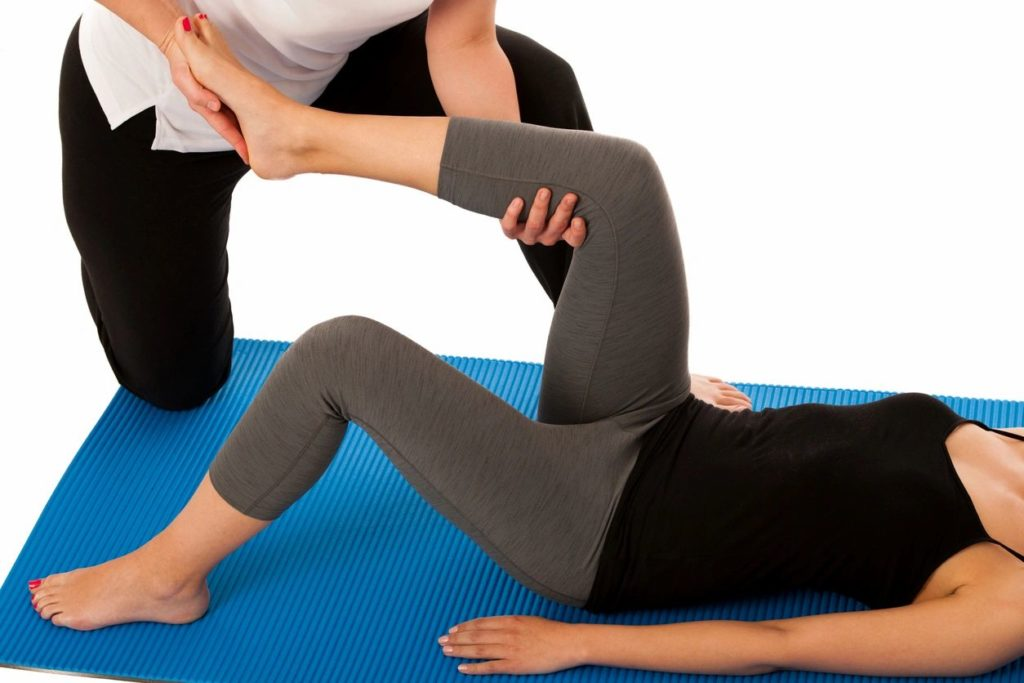 woman lying on yoga mat while her left leg is stretched by a stretch therapist