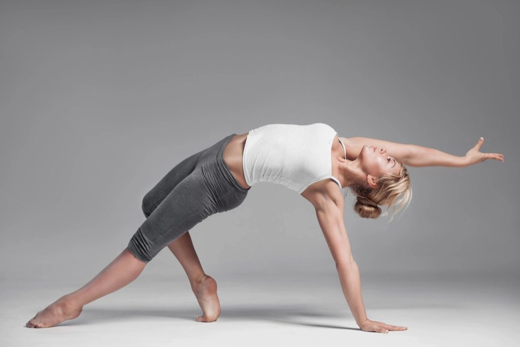 woman in exercise clothing stretching in a bridge position