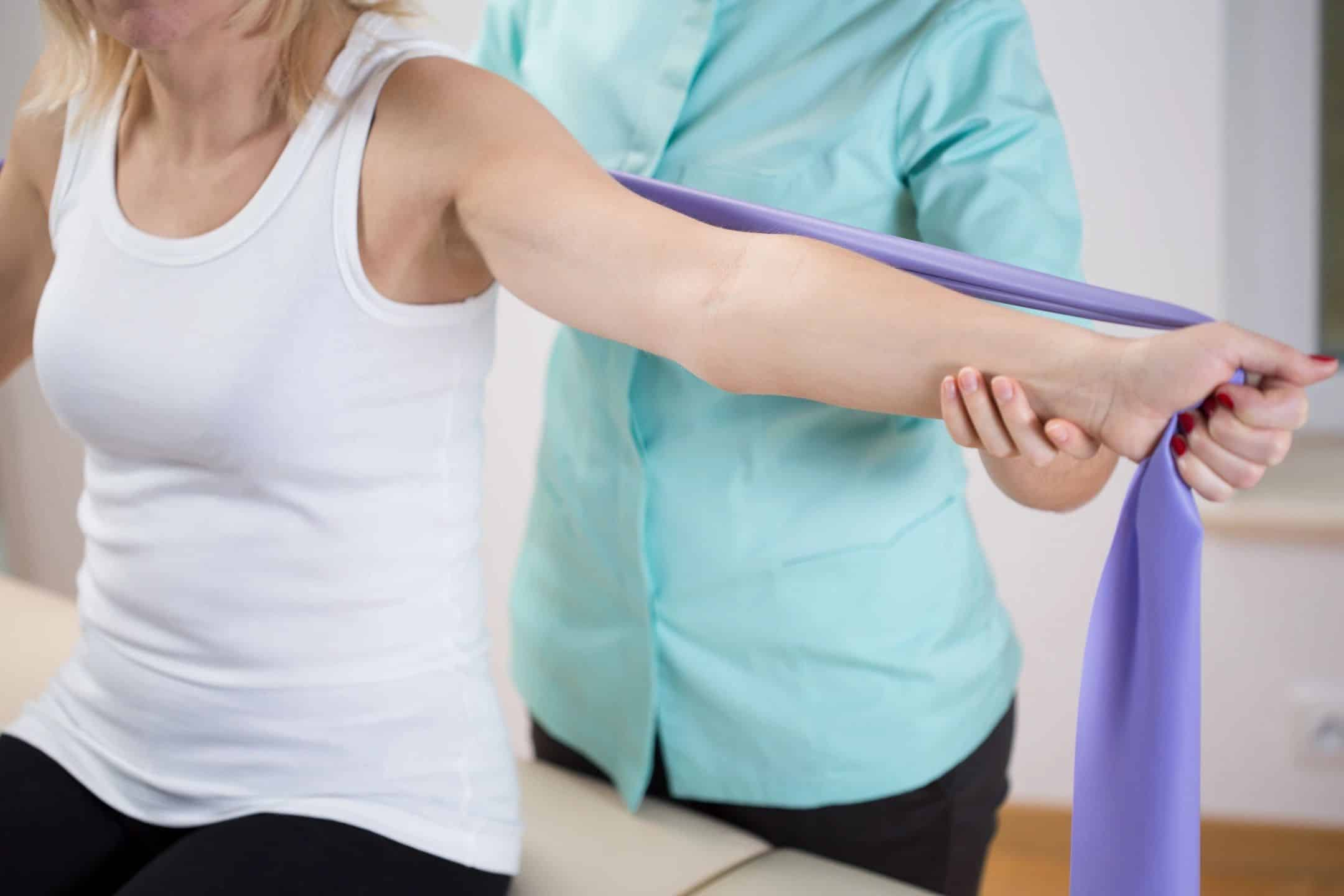 woman stretching using a large band with aid of therapist