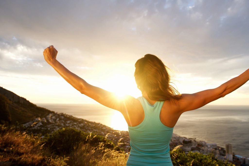 woman with raised arms looking at sunset