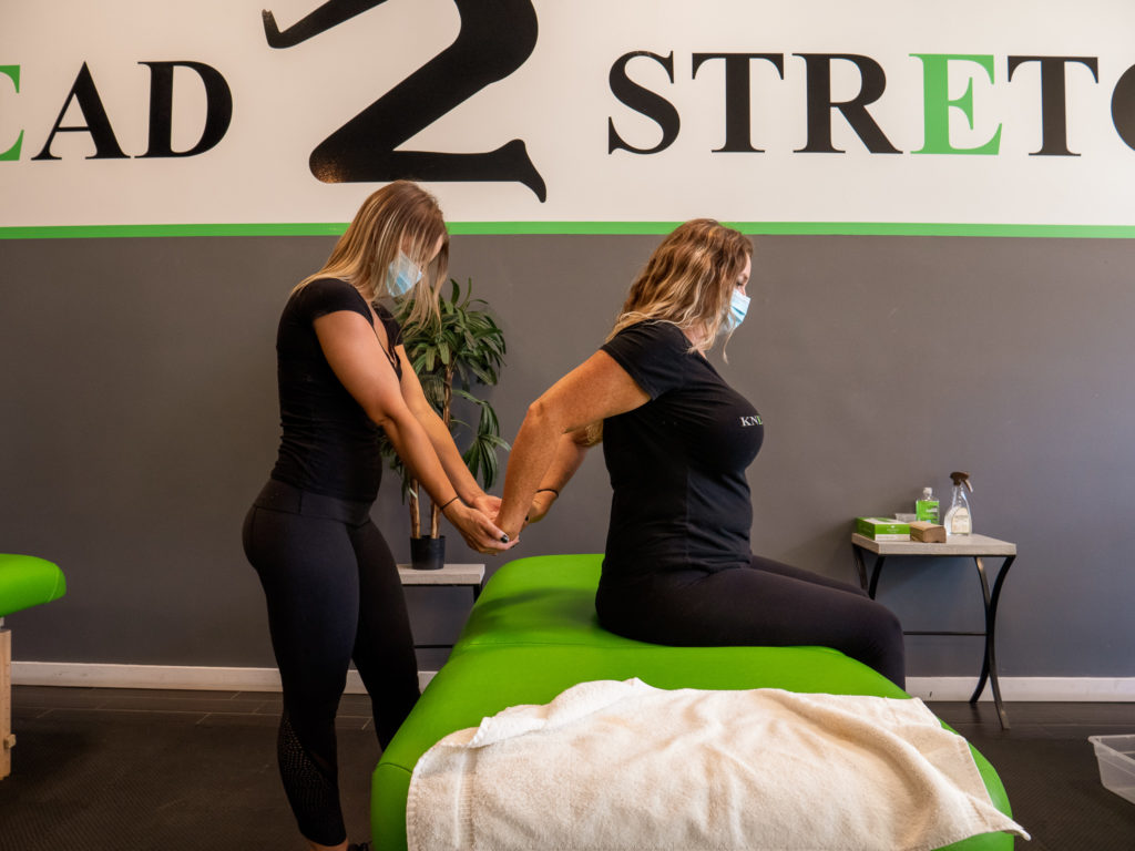 K2S employees demonstrating stretching techniques while wearing facemasks