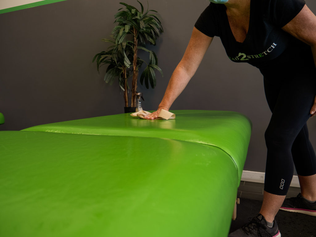 K2S worker disinfecting a stretching table before use