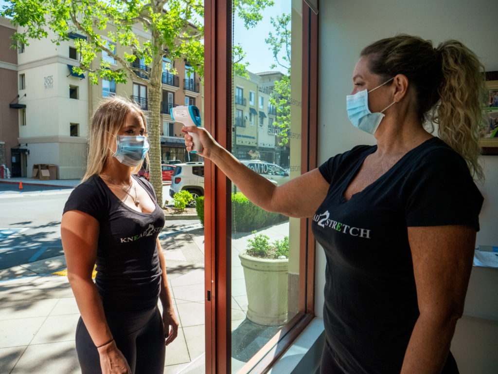 K2S Therapist taking the temperature of a person wearing a mask before entering the premise